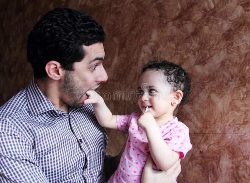 Arab egyptian baby girl playing with her father royalty free stock photo