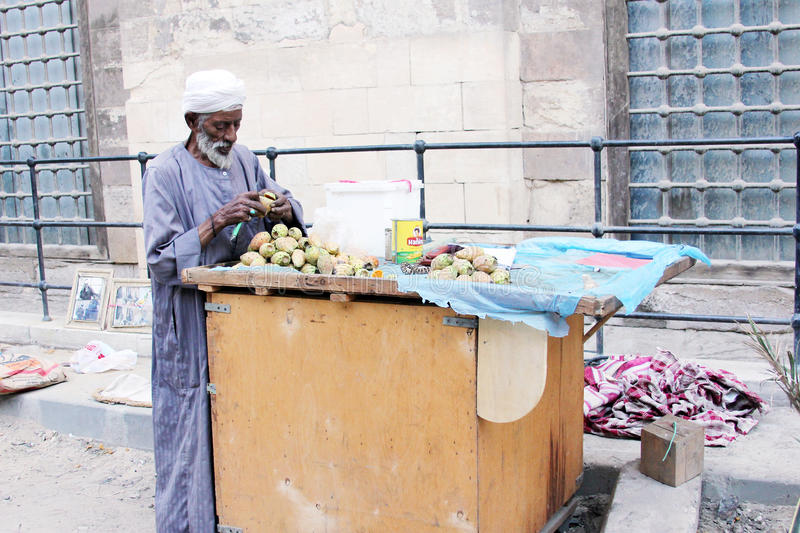 Arab egyptian selling prickly pears. Old poor muslim man with white beard selling prickly pears fruits in the street in poor district in cairo in egypt in africa