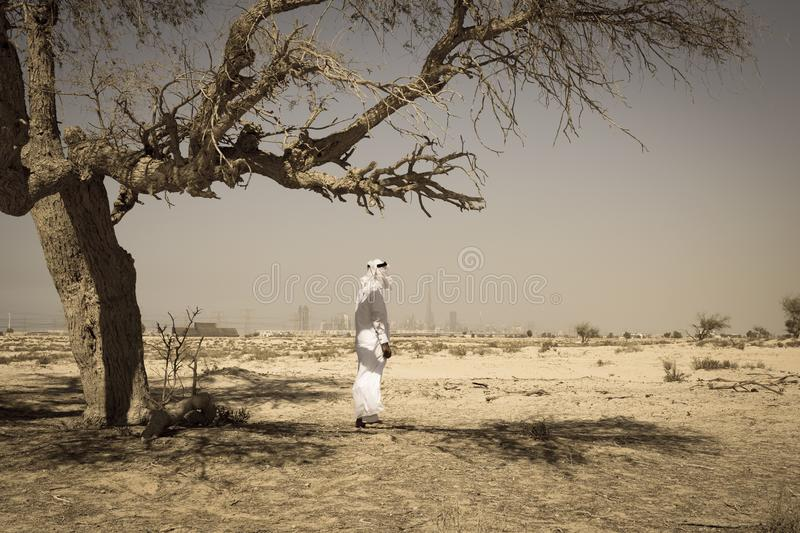 Arab man in the desert and looks at the city of Dubai. Arab man in national dress stands in the desert and looks at the city of Dubai royalty free stock image