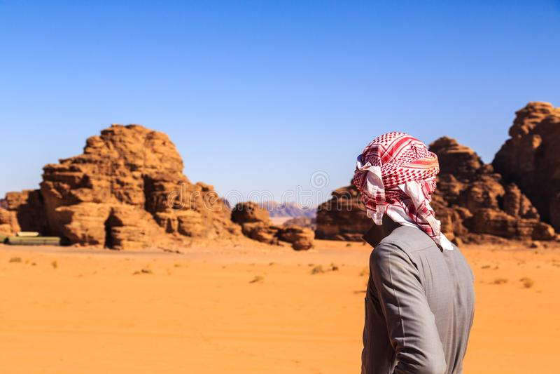 Arab man seen from behind in the Wadi Rum desert royalty free stock image