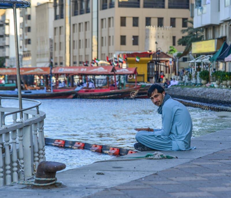 Arab man sitting at park of Dubai Creek stock images