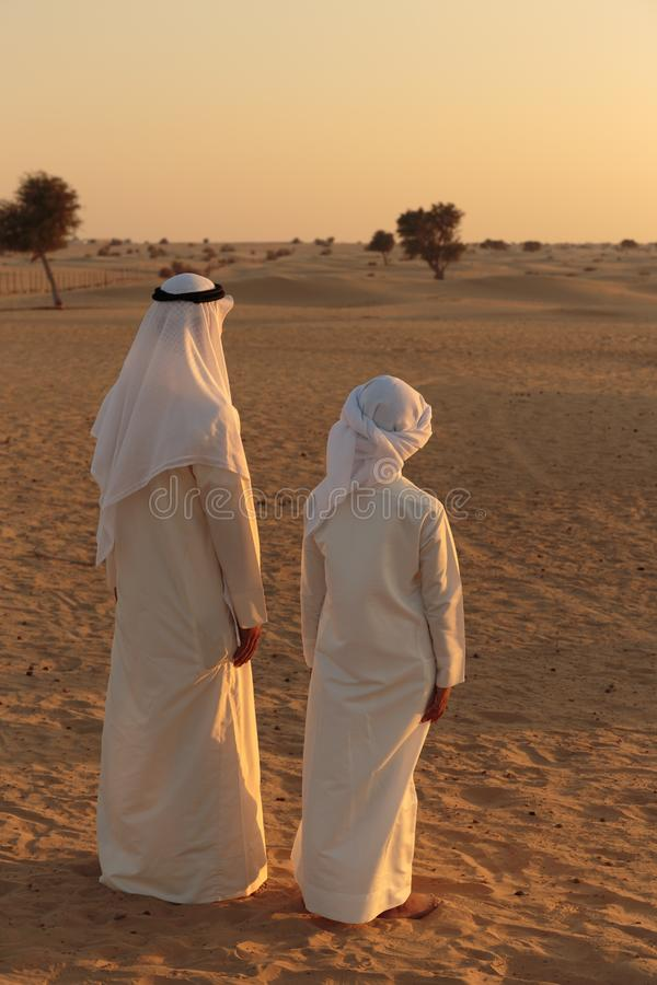Arab man and a teenager in the desert stock photos