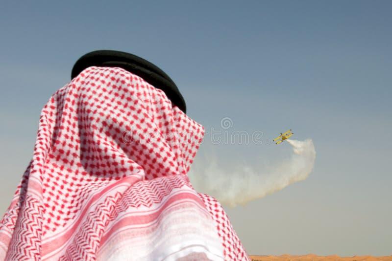 Arab man watching airshow. Over the desert royalty free stock image