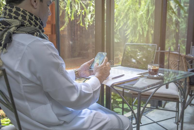 Arab muslim businessman working and using smart mobile phone on table in coffee shop,freelance business concept royalty free stock photos