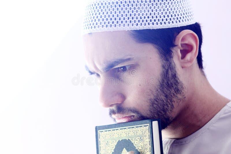 Arab muslim man with koran holy book. Arab egyptian muslim man wearing islamic clothes and holding Koran holy book stock image