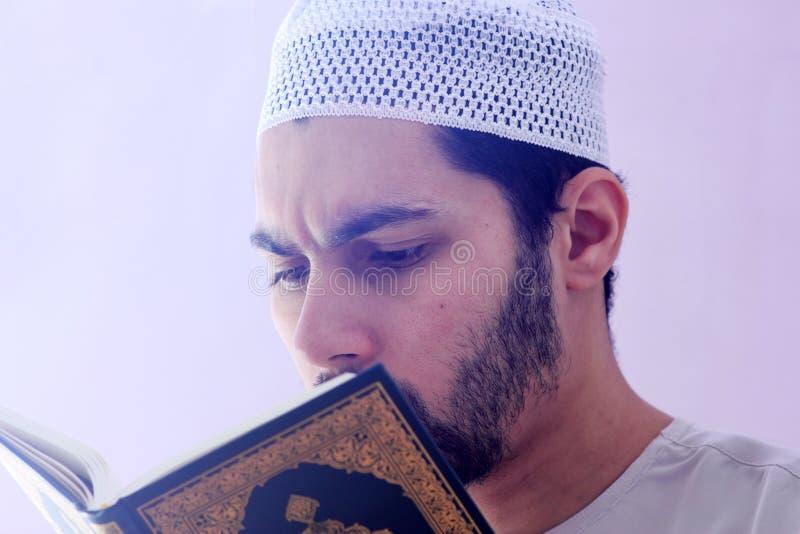 Arab muslim man with koran holy book royalty free stock photography