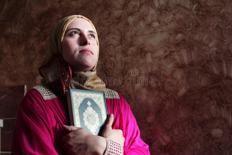 Arab muslim woman with koran holy book wearing hijab. Arabian egyptian muslim woman with Koran or quran, holy book of Islam religion wearing islamic clothes like royalty free stock photos