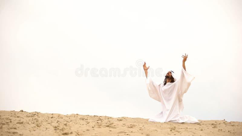 Arab raising hands to heaven, praying on knees, asking Allah to forgive sins stock photography