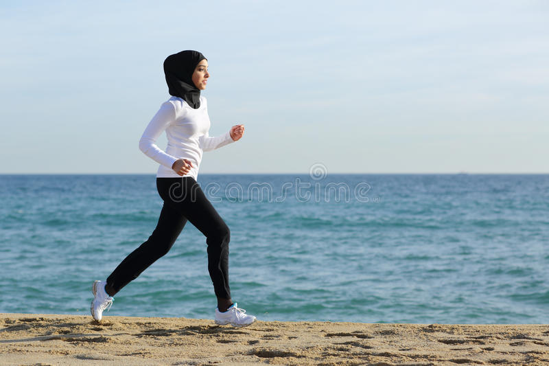 Arab saudi runner woman running on the beach. With the sea and horizon in the background royalty free stock photos