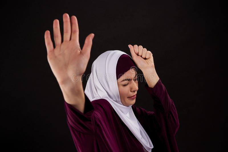 Arab scared woman in hijab defends herself. Oppression woman concept. Isolated on black background stock photo