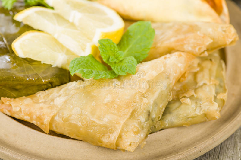 Arab Snacks. Sarma (grape vine leaves, stuffed with rice), borek (spinach and cheese stuffed pastry) and fatayer (meat pie stock photo
