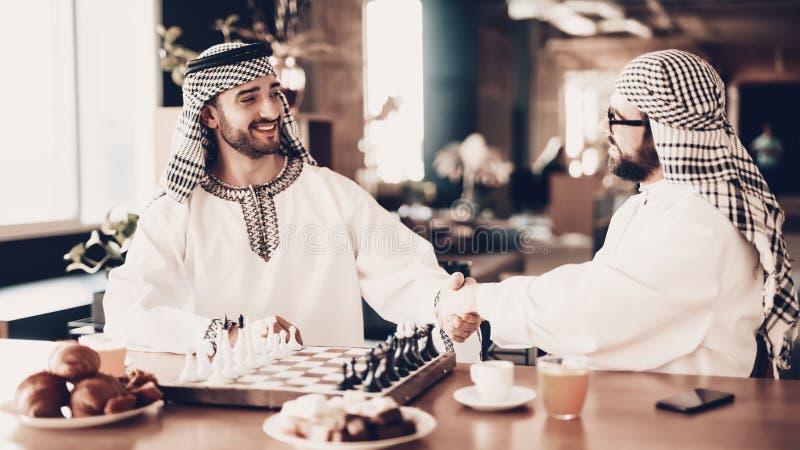 Arab som två skakar händer, innan att spela schack royaltyfria foton