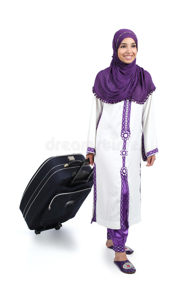 Arab traveler woman walking carrying a suitcase stock photography
