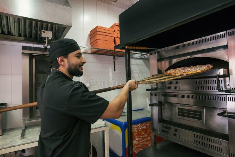 Arab turkish man preparing pizza in owen at his little business stock photo