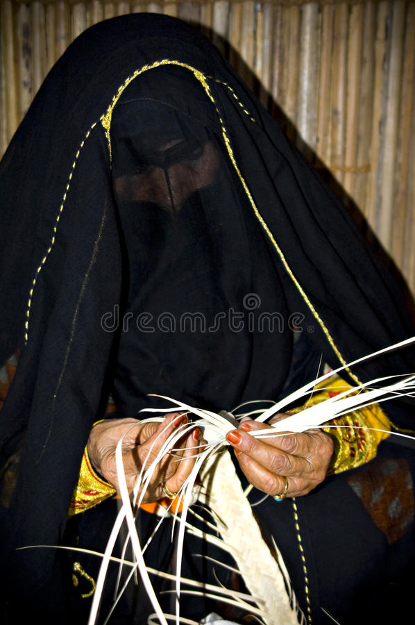 Arab woman craft. An old arabic woman crafting a traditional basket stock photo