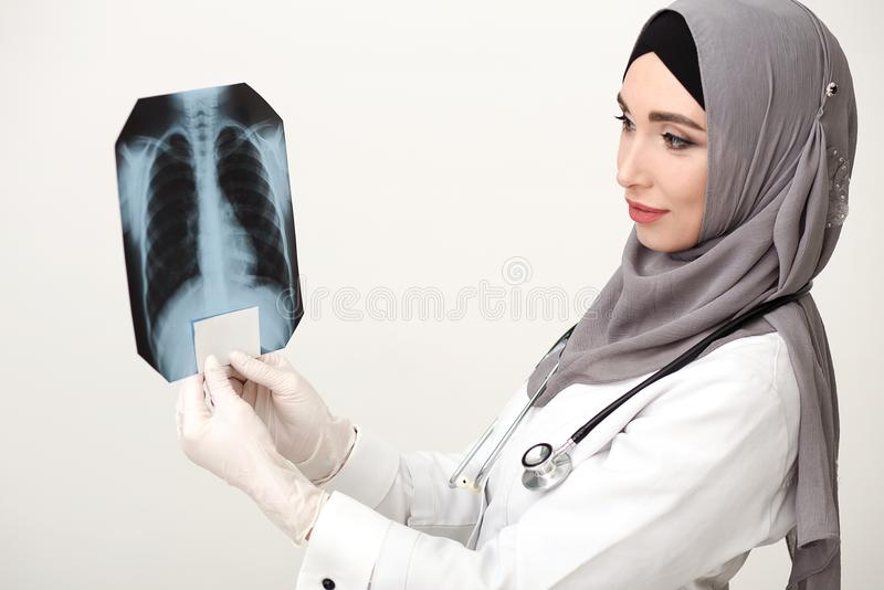 Islamic woman doctor looking at x-ray film royalty free stock photography