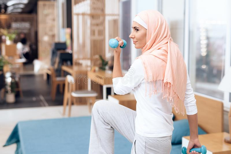 Arab woman doing gymnastics in the bedroom. royalty free stock photography
