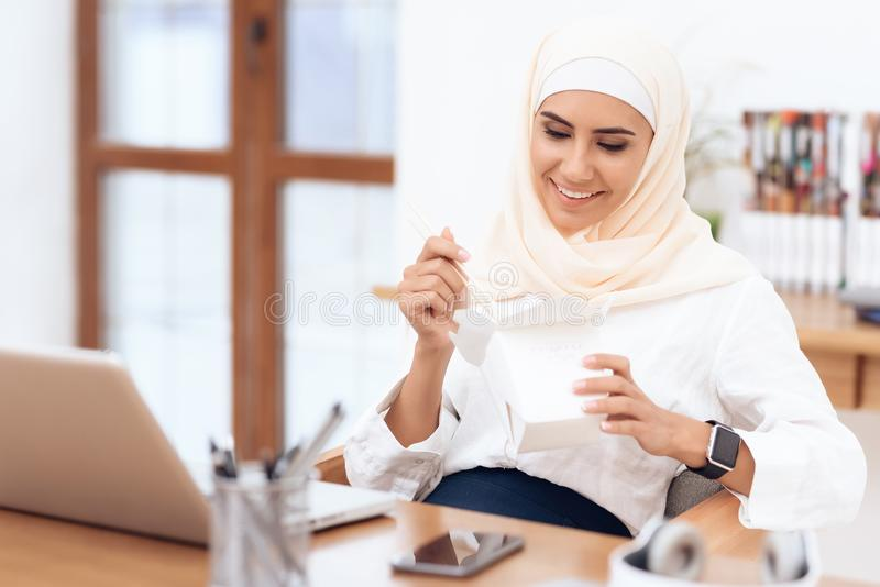 An Arab woman in a hijab is having lunch. stock image