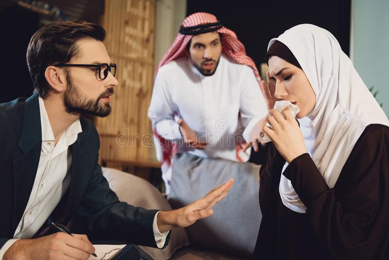 Arab woman with husband at psychologist reception. Arab women with husband at psychologist reception cries. Discussion of family problems in office of stock images