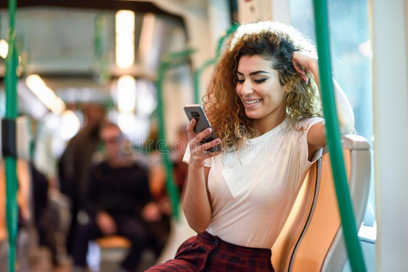 Arab woman inside subway train looking at her smartphone royalty free stock photos