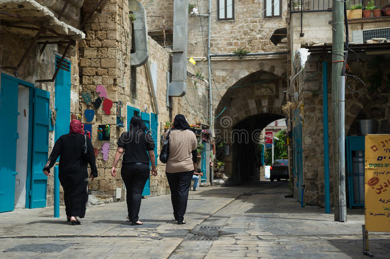 Arab women going on the old street of Akko, Israel stock photo