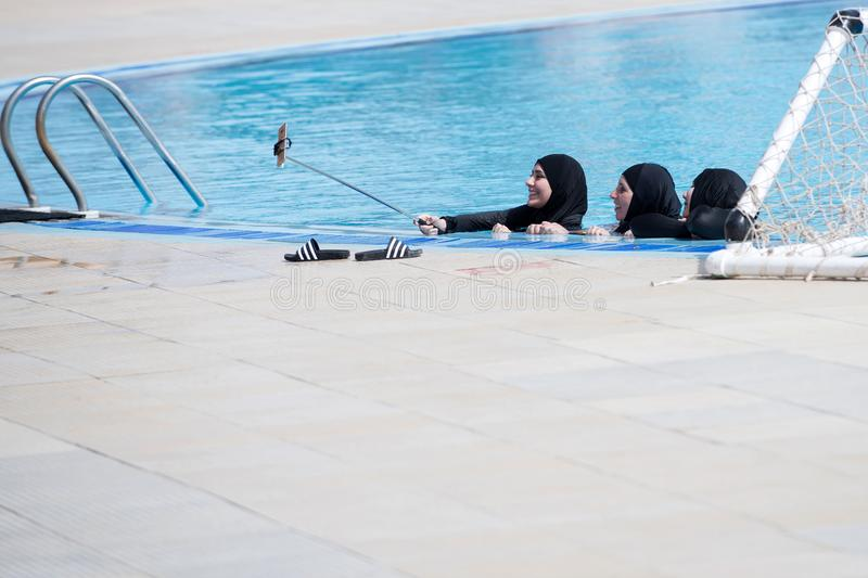 Arab women with happy faces in black burkini making selfie royalty free stock photos