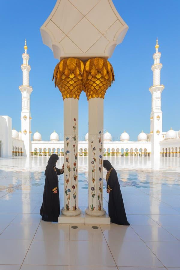 2 Arab women wearing traditional black burka clothing while praying in Sheikh Zayed Mosque in Abu Dhabi royalty free stock photo