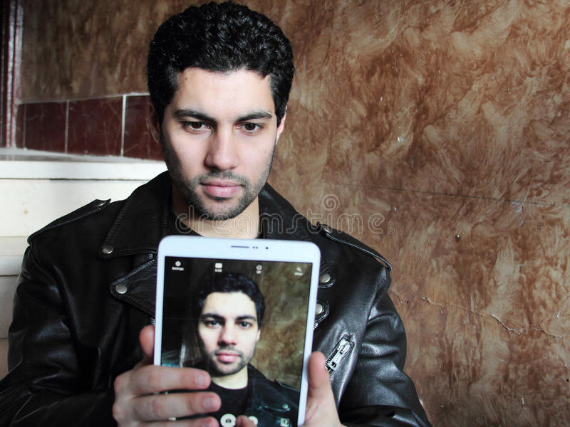 Arab young businessman in jacket taking selfie stock image