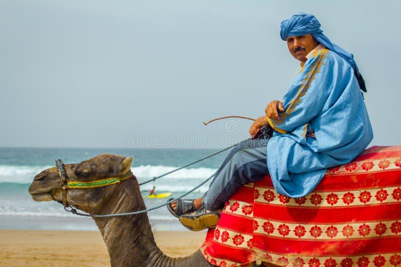 Araber mit einem Kamel gehen entlang das Meer lizenzfreies stockfoto