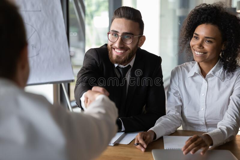 Arabian and african HR manager greeting applicant starting job interview royalty free stock photos
