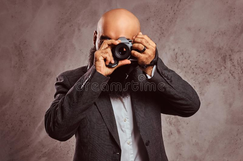 Arabian bearded male wearing a formal suit making a photo with camera. stock image