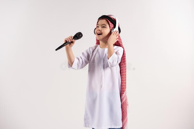 Arabian boy in keffiyeh with microphone sings karaoke royalty free stock image