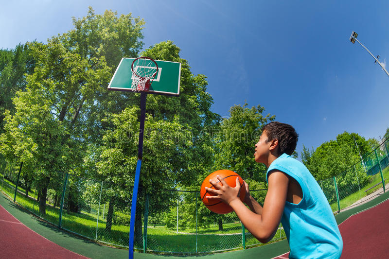 Arabian boy ready to throw ball in basketball goal. On the playground outside during sunny summer day royalty free stock photos