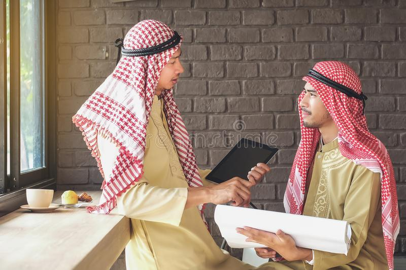 Arabian Business Advisory meeting two people talking business wi. Th coffee and a tablet royalty free stock photo