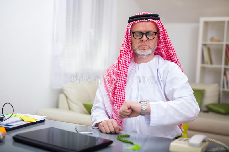 Arabian business man in his home office. Looking at his watch stock images