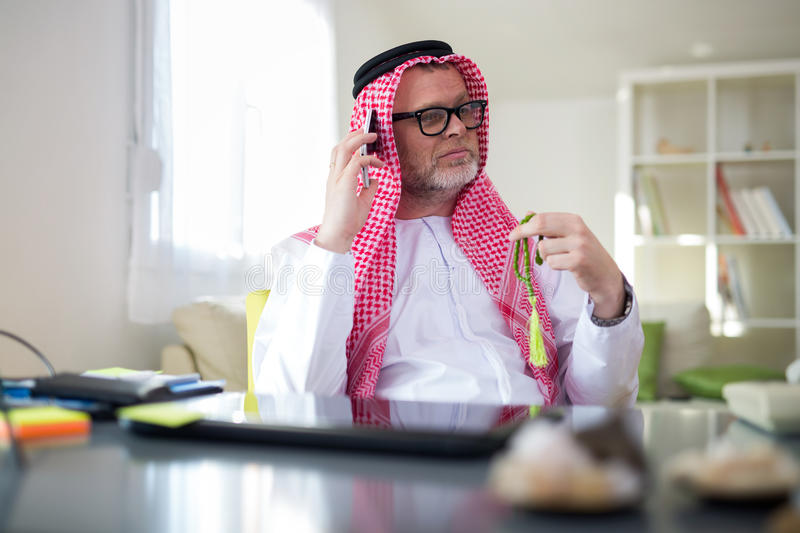 Arabian business man in his home office. Using smart phone stock photo