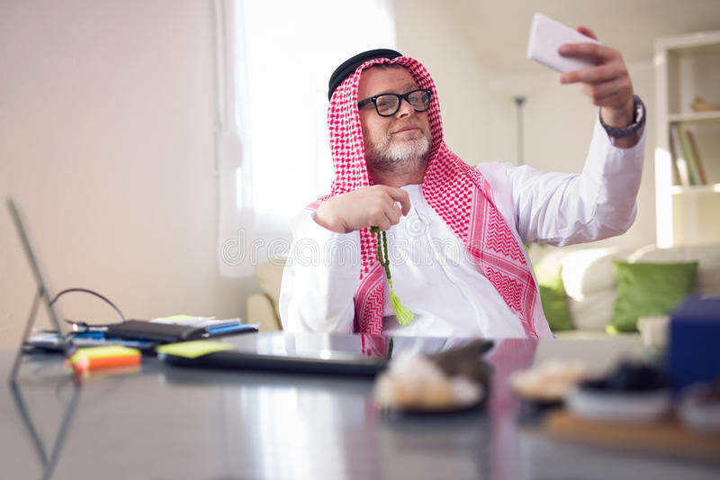 Arabian business man in his home office. Using smart phone stock images