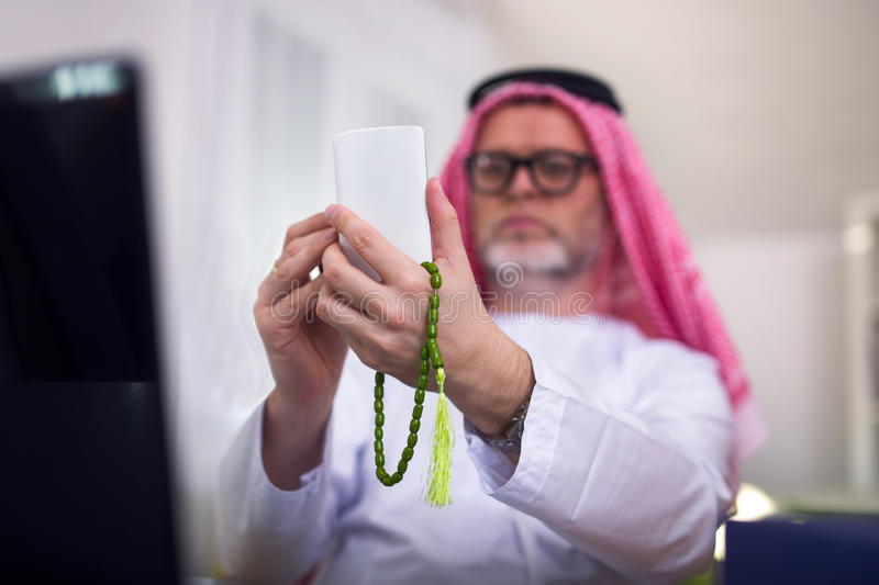 Arabian business man in his home office. Using smart phone stock photography
