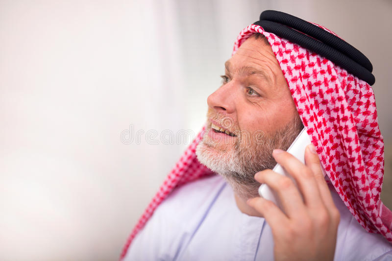 Arabian business man in his home office. Using smart phone royalty free stock image