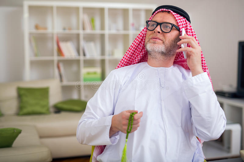 Arabian business man in his home office. Using smart phone royalty free stock photos