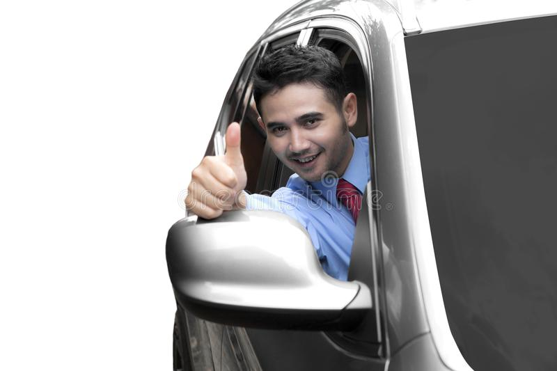 Arabian businessman driving a new car. While showing thumb up, isolated on white background stock photos