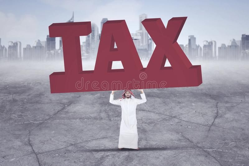 Arabian businessman lifting a big and heavy word of tax with skyscrapers in the background. Business concept stock image