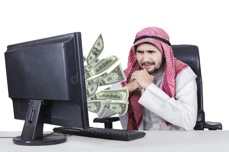 Arabian businessman with money on his computer royalty free stock photo