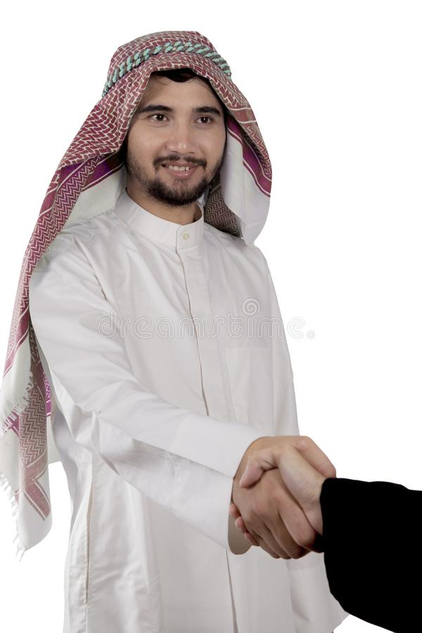 Arabian businessman shaking hands with his colleague. Picture of Arabian businessman shaking hands with his colleague, isolated on white background royalty free stock image