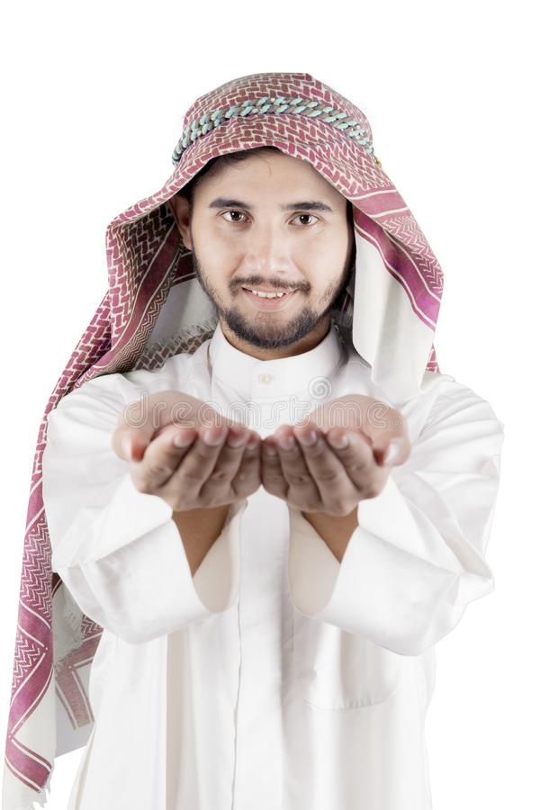 Arabian businessman showing something on his palms. Closeup of Arabian businessman showing something on his palms, isolated on white background stock images