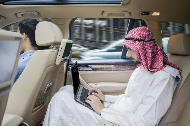 Arabian businessman working with laptop in car royalty free stock photo