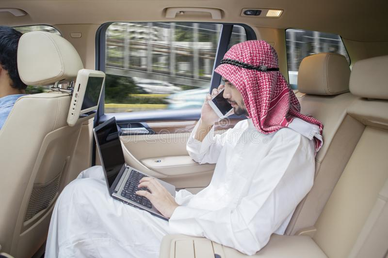 Arabian businessman with laptop and phone in car stock photos