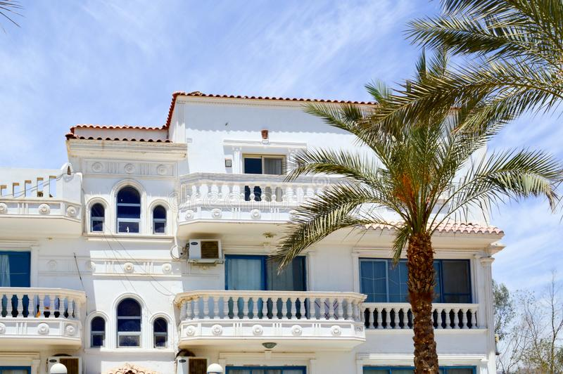 Arabian cottage with a tiled red roof, a house in the desert with balconies and windows against the backdrop of a green palm tree royalty free stock photo