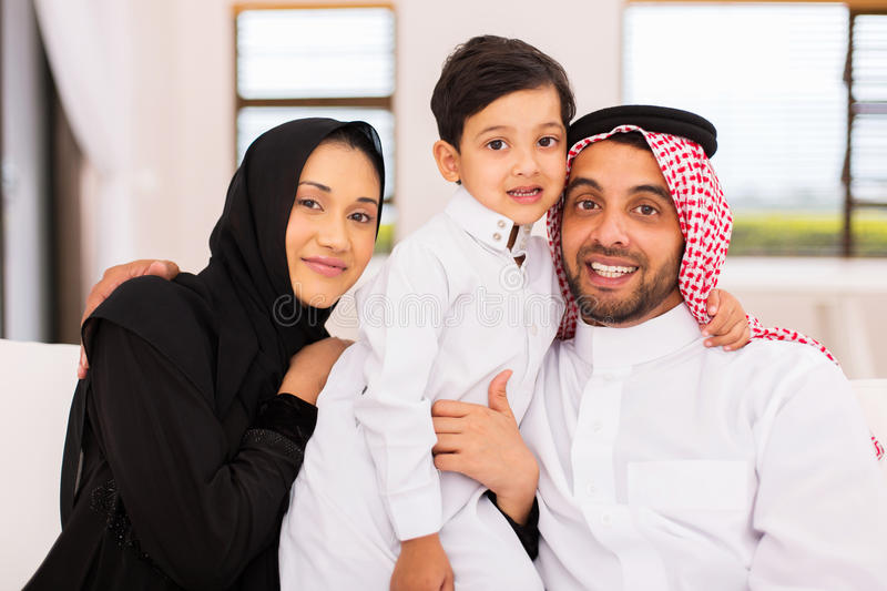 Arabian couple son couch. Portrait of arabian couple with their son sitting on couch at home royalty free stock image