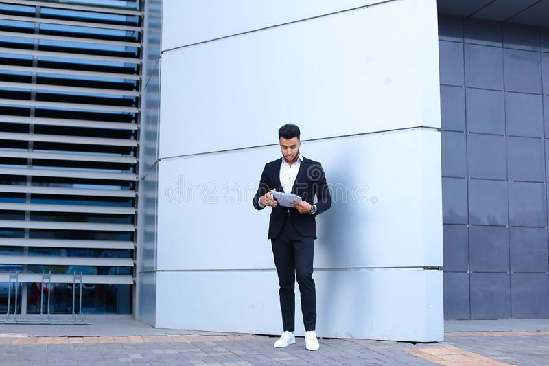 Arabian entrepreneur man holds and considers, reads documents, stands in full growth in profile near wall of business. Young tall handsome arab entrepreneur guy royalty free stock images